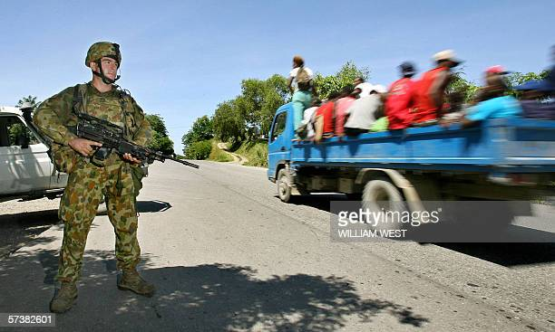 An Australian soldier guards a road into the Solomon Island's capital Honiara to restore order after two days of rioting 21 April 2006 Rioters...