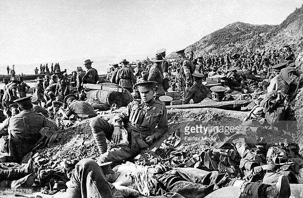 An Australian soldier lies wounded in the foreground as hundreds of other soldiers move among the dead and wounded on the beach at Anzac Cove on the...