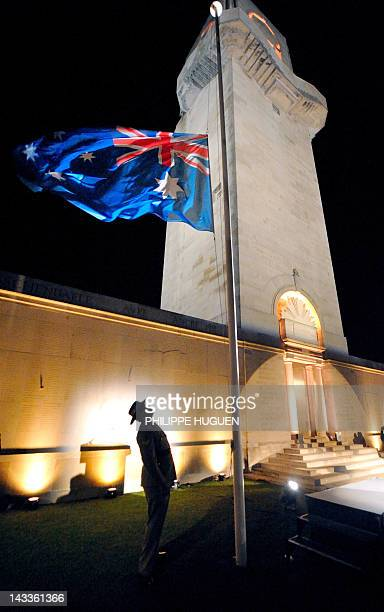 An Australian soldier looks up at an Australian flag in front of a wall bearing the WWI dead soldiers' names during a dawn service at the Australian...