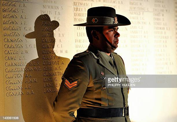 An Australian soldier stands in front of a wall bearing the WWI dead soldiers' names as he attends a dawn service at the Australian War Memorial in...