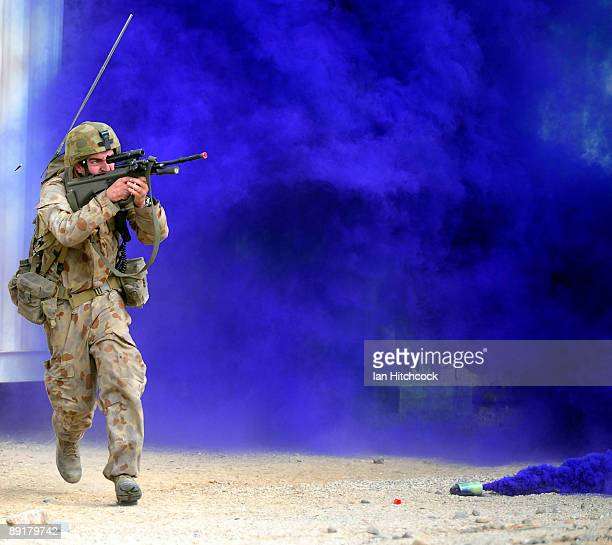 An Australian soldier who is role playing as an enemy soldier fires his rifle as he runs for cover as US Marines from the 31st Marine Expeditionary...