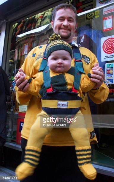 An Australian supporter holding his baby poses 06 November 1999 in a Cardiff street a few hours before the Rugby World Cup 1999 final game opposing...