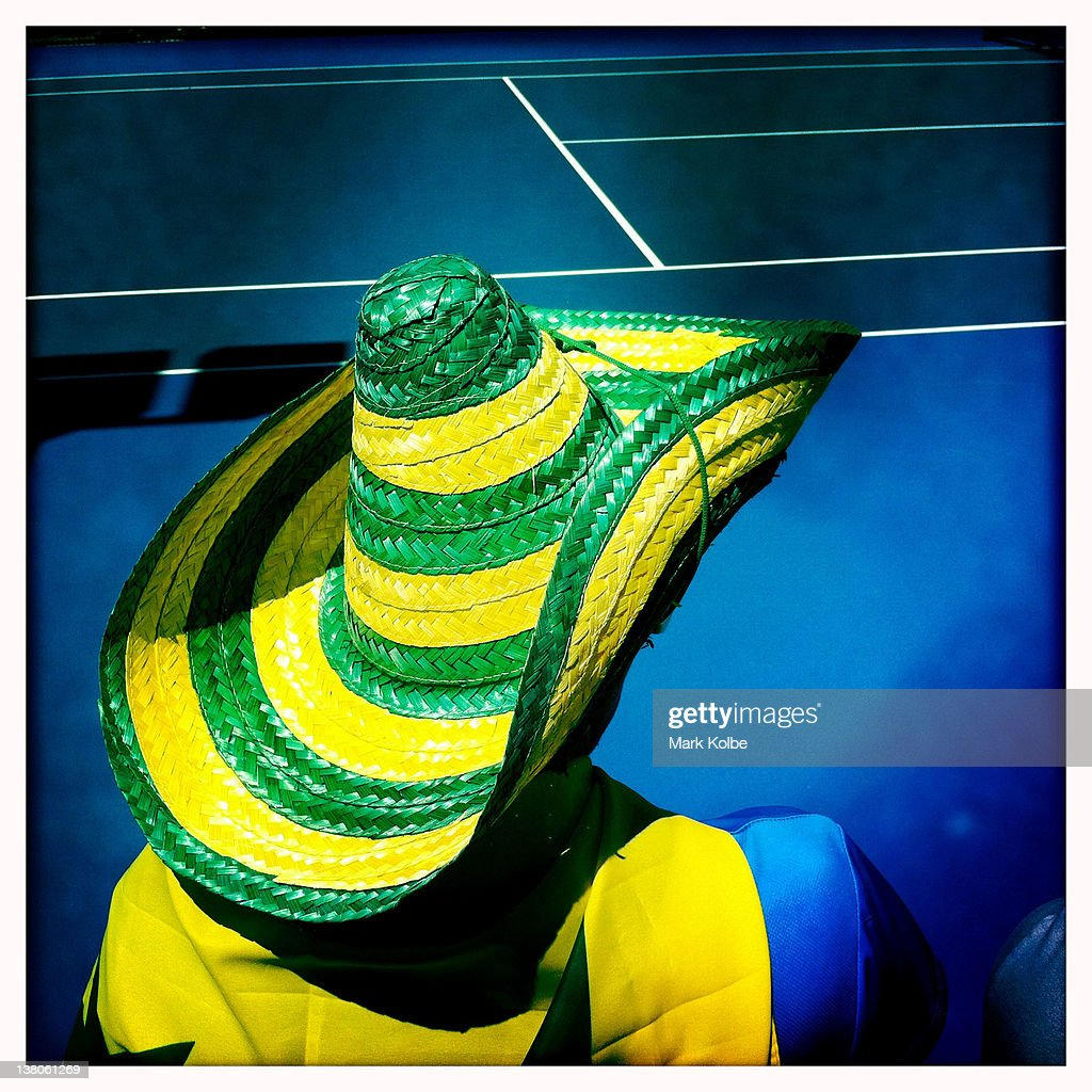 An Australian supporter wearing a green and gold painted sombrero watches action on the outside courts during the 2012 Australian Open at Melbourne Park on January 16, 2012 in Melbourne, Australia.