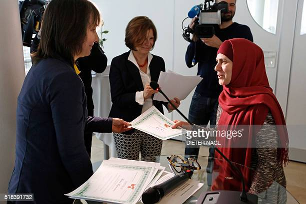 An Austria based graduate from Chechnya recieves her diploma from Maynat Kurbanova of the so called 'motherschool' on March 8 2016 in Vienna / AFP /...