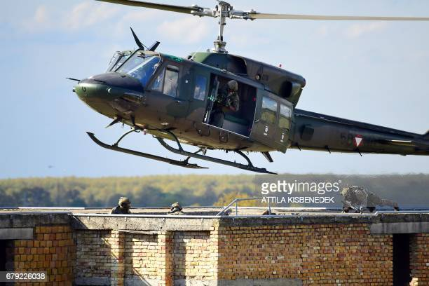 An Austrian Air Force utility helicopter lands on a building during a hospital evacuation exercise at Papa Airbase a military training center nearby...