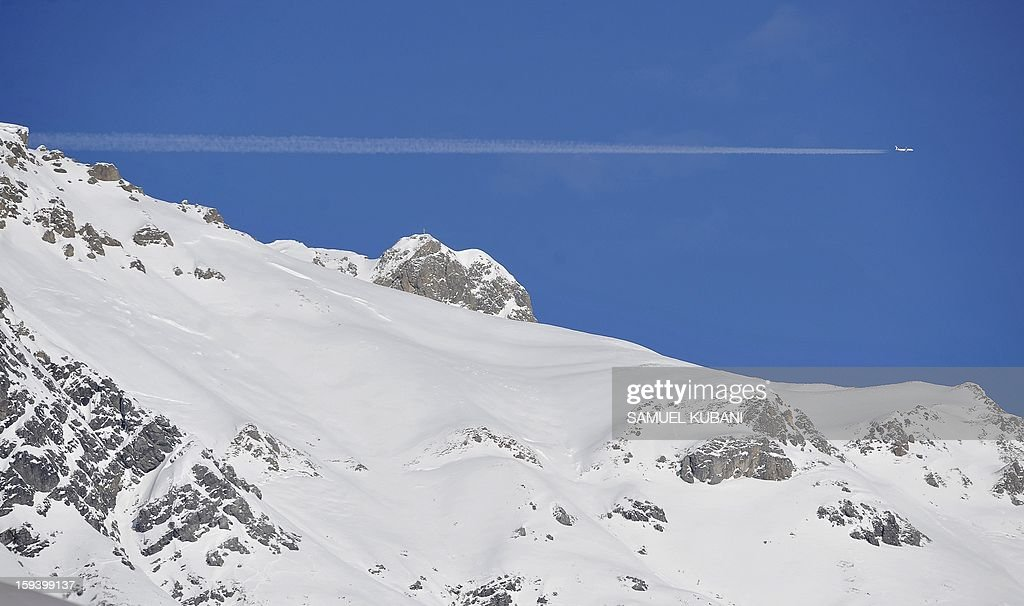 An Austrian Airlines airplane flies over mounties during the women's World Cup Super G January 13, 2012 in St Anton am Arlberg.