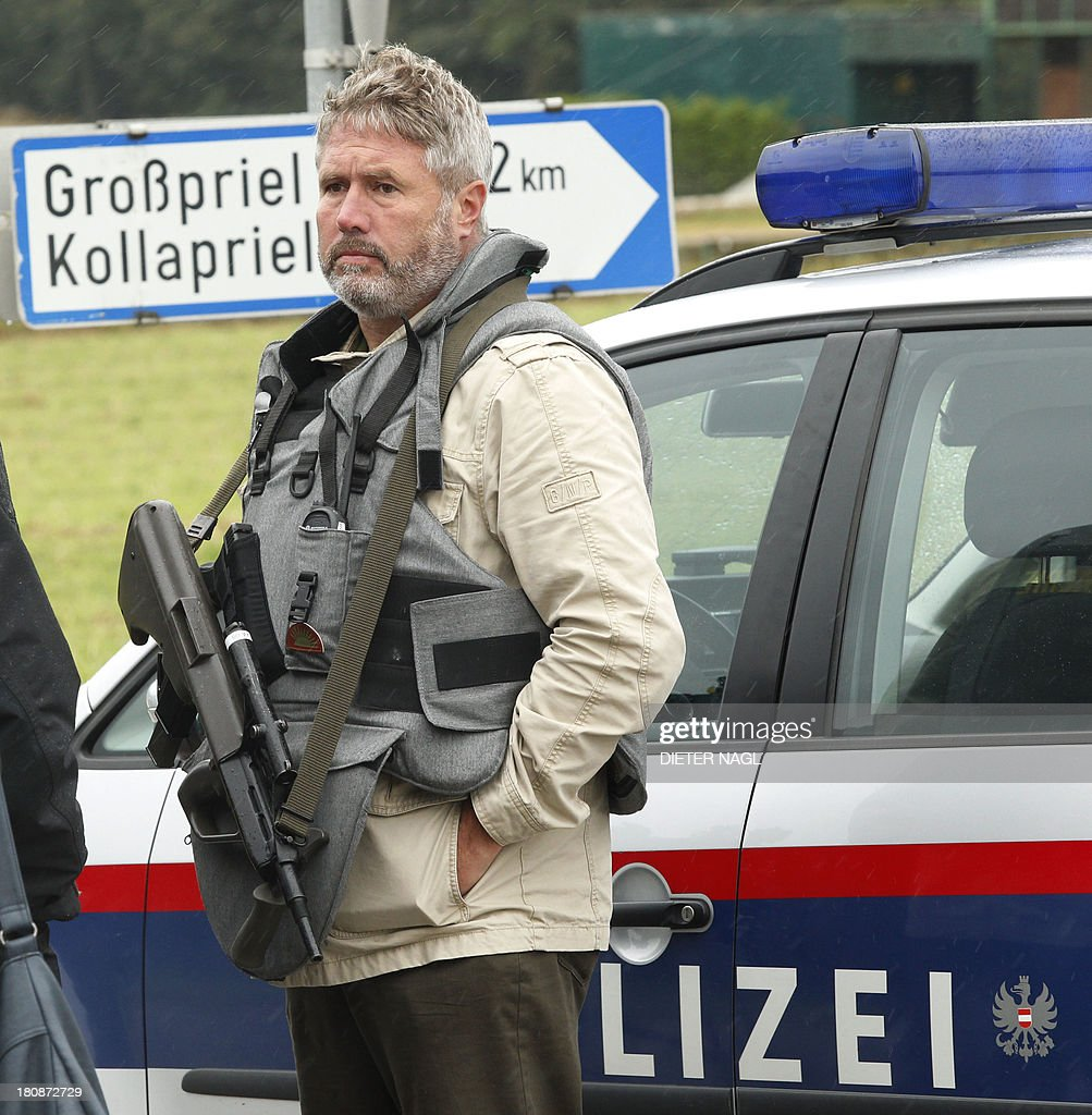 An Austrian police officier blocks a road on September 17, 2013 near Grosspriel where a poacher has shut himself in a farmhouse with a hostage. Police had attempted to stop the man in his car late on September 16, 2013 near Annaberg, some 100 kilometres (60 miles) west of Vienna, but he shot dead two police officers and an emergency worker and has taken another officer hostage on his run, reports said.