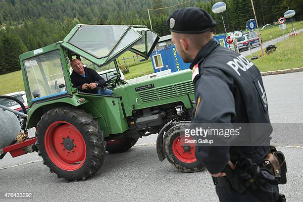An Austrian policeman chats with a local farmer at a police checkpoint on a road leading to the InteralpenHotel Tirol venue of the upcoming...