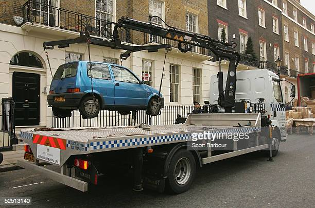 An 'Authorised Removal Unit' from Westminster City Council lifts up and removes an illegally parked car on March 31 2005 in London England
