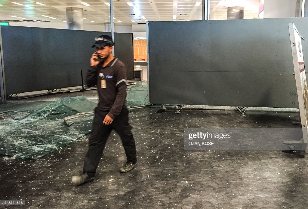 An authorized personnel walks past glass debris at the explosions and attacks site in Ataturk airport's international arrivals terminal on June 29, 2016, a day after a suicide bombing and gun attack targeted Istanbul's airport, killing at least 36 people. A triple suicide bombing and gun attack that occurred on June 28, 2016 at Istanbul's Ataturk airport has killed at least 36 people, including foreigners, with Turkey's prime minister saying early signs pointed to an assault by the Islamic State group. / AFP / OZAN