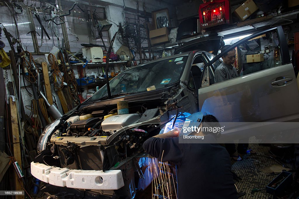 An auto mechanic works on a vehicle inside a car-repair shop in the Tai Hang area of Hong Kong, China, on Saturday, March 30, 2013. Rents are climbing in neighborhoods near Causeway Bay and Hong Kong's other prime shopping districts, known for luxury stores that attract free-spending tourists from mainland China. That's squeezing out mom-and-pop shops, congee and noodle vendors as developers and landlords seek to profit from the trend. Photographer: Lam Yik Fei/Bloomberg via Getty Images