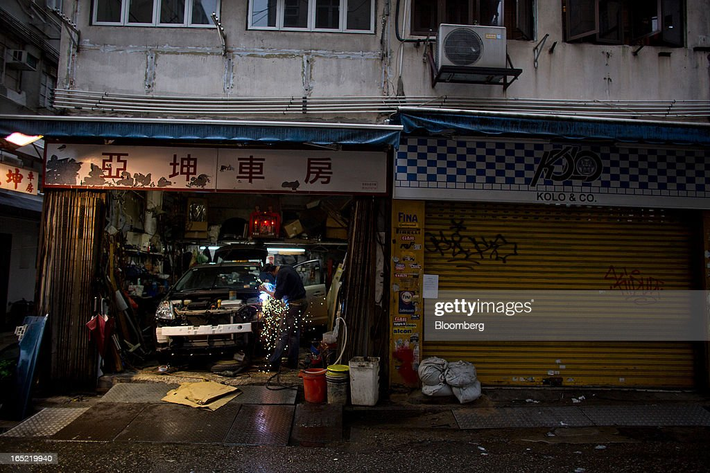 An auto mechanic works on a vehicle inside a car-repair shop next to a shuttered retail space in the Tai Hang area of Hong Kong, China, on Saturday, March 30, 2013. Rents are climbing in neighborhoods near Causeway Bay and Hong Kong's other prime shopping districts, known for luxury stores that attract free-spending tourists from mainland China. That's squeezing out mom-and-pop shops, congee and noodle vendors as developers and landlords seek to profit from the trend. Photographer: Lam Yik Fei/Bloomberg via Getty Images