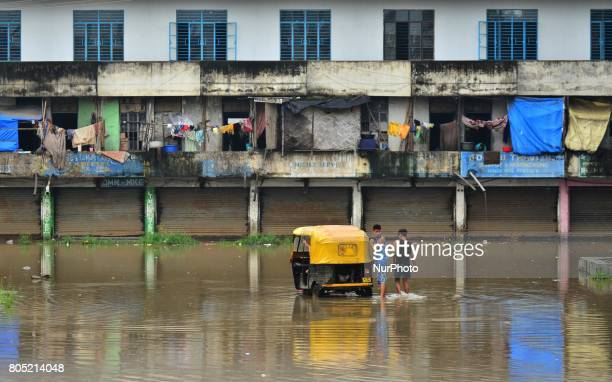 An auto rickshaw ferrying commuters check their vehicle as it break down on a flood water in a residential area after a heavy rainfall in Dimapur...