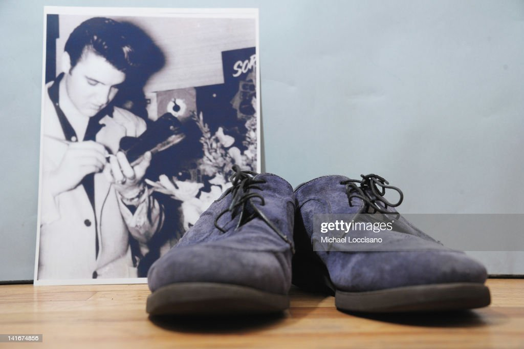 An autographed pair of Elvis Presley's original blue suede shoes and a photo of him autographing them on auction at Gotta Have It store on March 21...