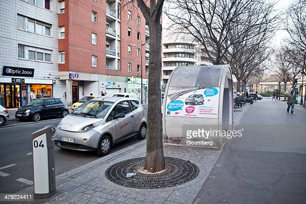 An Autolib' electric automobile manufactured by Groupe Bollore sits at a public carsharing scheme charging station beside a customer shelter in Paris...