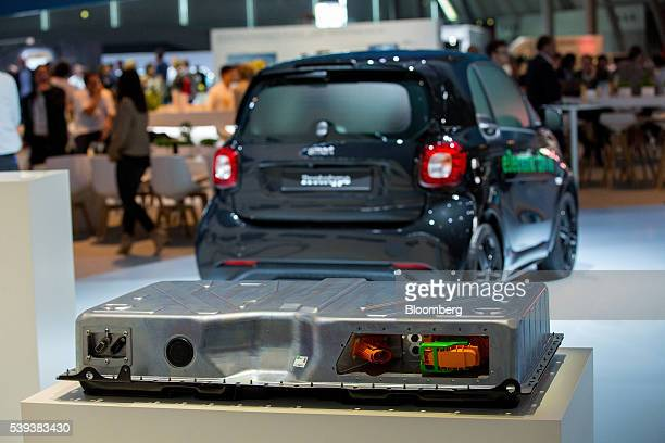 An automobile battery pack sits on display as a Daimler AG Smart plugin automobile stands beyond during Daimler's TecDay Road to the Future event in...