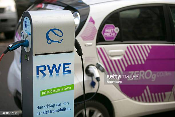 An automobile charging station operated by RWE AG stands connected to a Citroen CZero electric carsharing automobile manufactured by PSA Peugeot...