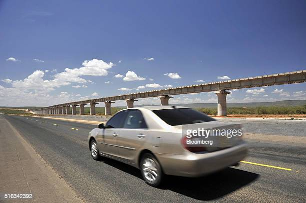 An automobile passes along a highway past a section of the new Tsavo superbridge which will form part of the new MombasaNairobi Standard Gauge...