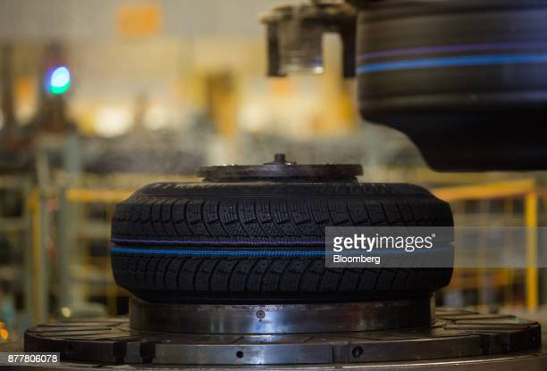 An automobile tire sits on an hydraulic machine following vulcanization at the Continental AG tire plant in Kaluga Russia on Wednesday Nov 22 2017...