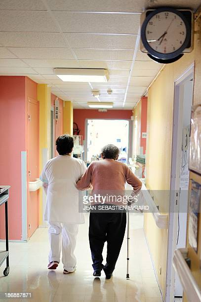 An auxiliary nurse helps a patient walk in a geriatric unit at the CHU Angers teaching hospital in Angers western France on October 23 2013 The...