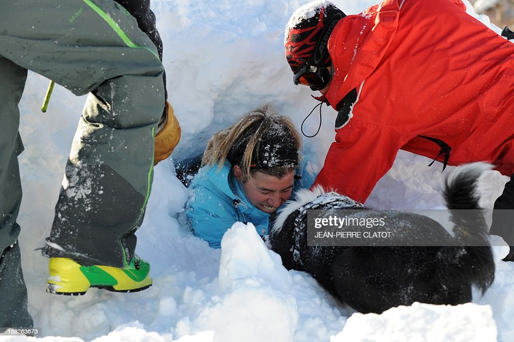 EMONET An avalanche dog and his master free a person buried in the snow, on December 11, 2012, during an avalanche dogs training session near Les Deux Alpes ski resort in the French Alps. France, with 140 avalanche rescue teams with dogs, is a reference in this activity sector which trains foreigners from Europe and other continents.