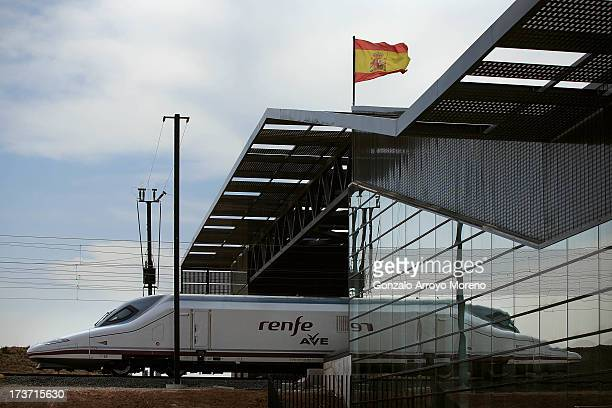 An AVE the Spanish high speed train enters to the Villena glassandsteel station coming from Alicante as a Spanish flag flutters crowning the building...