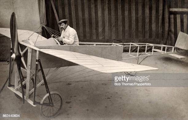 An aviation pioneer posing at the wheel of an early monoplane in a hangar near Paris circa 1910