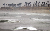 An avid surfer rides a wave in the Pacific Ocean at Huntington Beach California on August 5 2011 as the pros compete in the US Open of Surfing More...