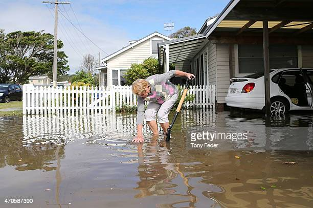An Avoca Beach resident cleans up her property on the Central Coast after flooding on April 22 2015 in Sydney Australia Three people have died and...