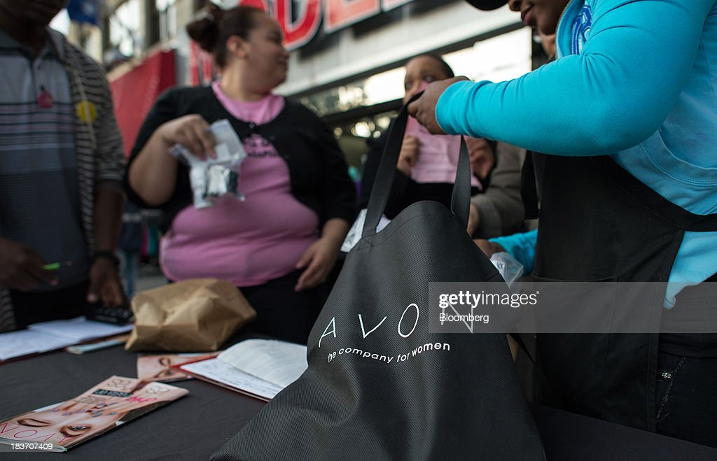 An Avon Products Inc. representative fills a bag during an Avon Magic Bus recruiting event in the Bronx borough of New York, U.S., on Tuesday, Oct. 8, 2013. Beauty and personal-care sales and earnings are expected to exceed those of household products in 2013 with recovering mass-beauty companies like Avon positioned at the top end of 2013 consensus earnings expectations. Photographer: Ron Antonelli/Bloomberg via Getty Images