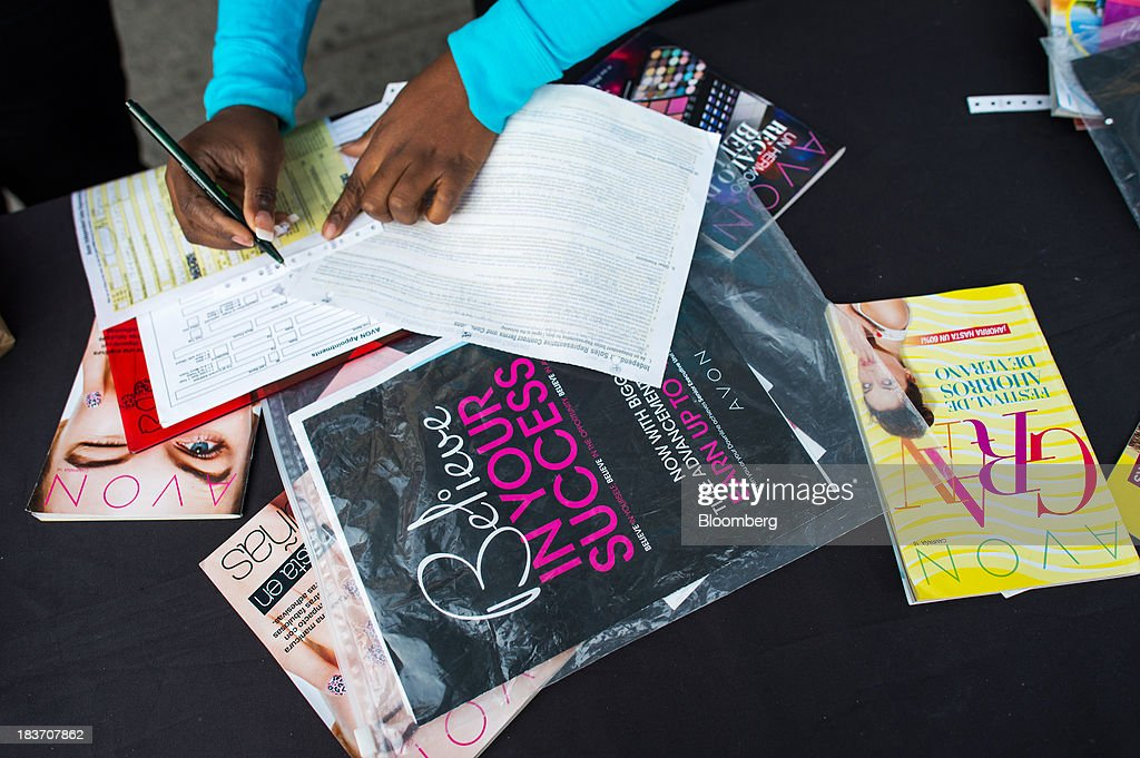 An Avon Products Inc. representative fills out paperwork during an Avon Magic Bus recruiting event in the Bronx borough of New York, U.S., on Tuesday, Oct. 8, 2013. Beauty and personal-care sales and earnings are expected to exceed those of household products in 2013 with recovering mass-beauty companies like Avon positioned at the top end of 2013 consensus earnings expectations. Photographer: Ron Antonelli/Bloomberg via Getty Images