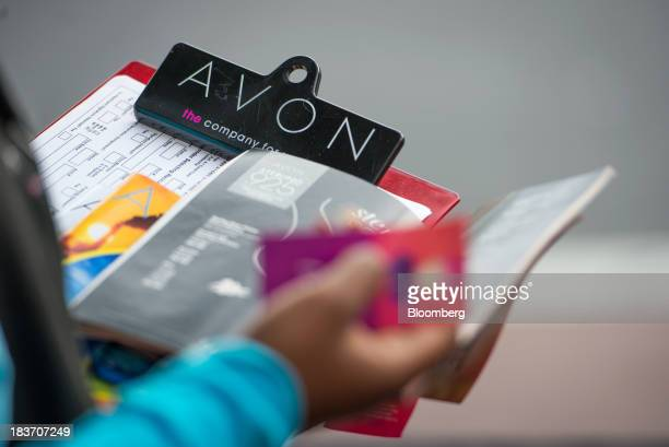 An Avon Products Inc representative holds a clipboard while recruiting new sales people during an Avon Magic Bus event in the Bronx borough of New...
