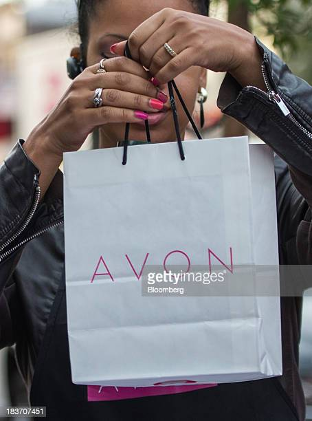 An Avon Products Inc sales representative holds a bag during an Avon Magic Bus recruiting event in the Bronx borough of New York US on Tuesday Oct 8...