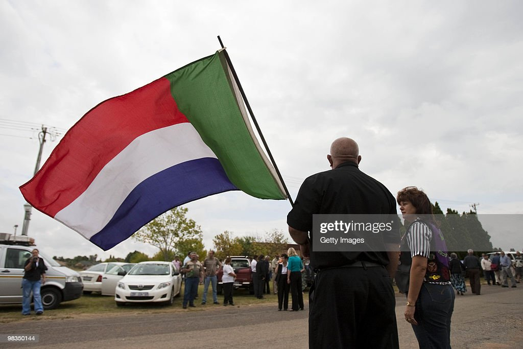 An AWB member waves the pre apartheid flag during the funeral of Afrikaner Resistance Movement (AWB) slain leader Eugene Terre'Blanche on April 9, 2010 in Ventersdorp, South Africa. Some 3,000 people attended the funeral of the white supremacist who was murdered last Saturday at his farm. Two of Terrblanche's employees have been charged with his murder.