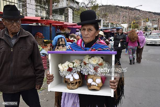 An Aymara indigenous woman arrives at a cemetery in La Paz on November 8 carrying a box with two human skulls to be blessed during the celebration of...