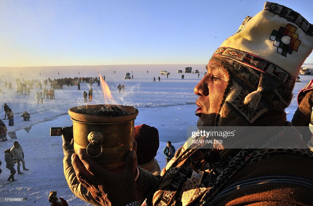 An Aymara priest participates in a ritual at sunrise to celebrate the Aymara New Year on June 21, 2013 at the Uyuni salt flat in Bolivia. A crowd gathered to receive the first rays of Tata Inti (god Sun) during the celebration of the winter solstice that marks the beginning of the 5521st year in the Aymara calendar. AFP/PHOTO/Aizar RALDES