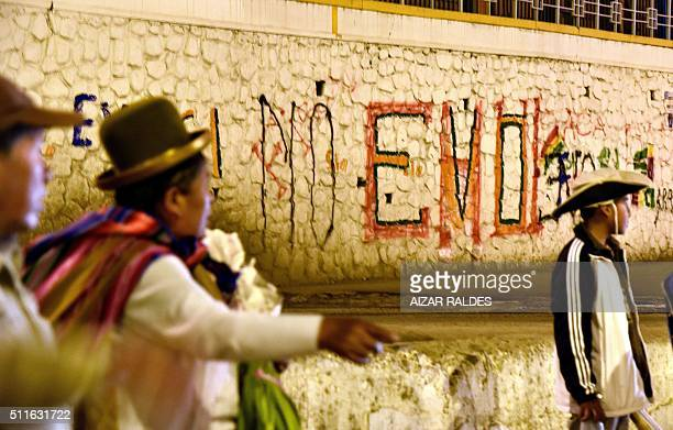 An aymara woman is seen walking next to a graffiti that reads 'No Evo' after the referendum rejection in El Alto Bolivia on February 21 Bolivians on...