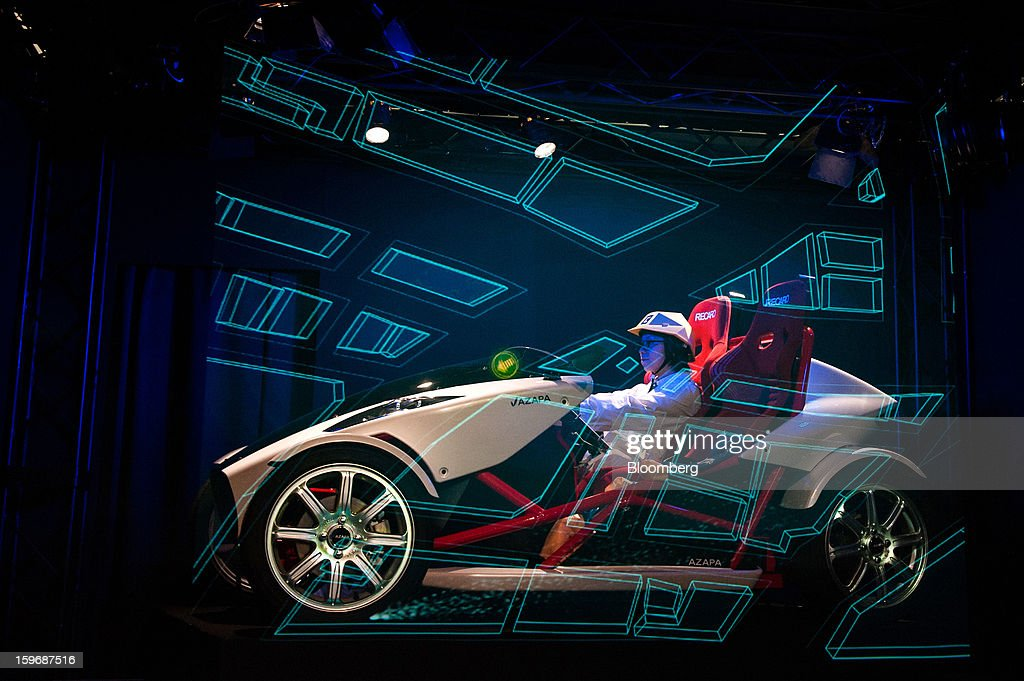 An Azapa Co. AZP-LSEV electric vehicle (EV) is displayed behind a screen simulating a map during a demonstration at Automotive World 2013 in Tokyo, Japan, on Friday, Jan. 18, 2013. The Automotive World 2013 trade show ends today. Photographer: Noriko Hayashi/Bloomberg via Getty Images