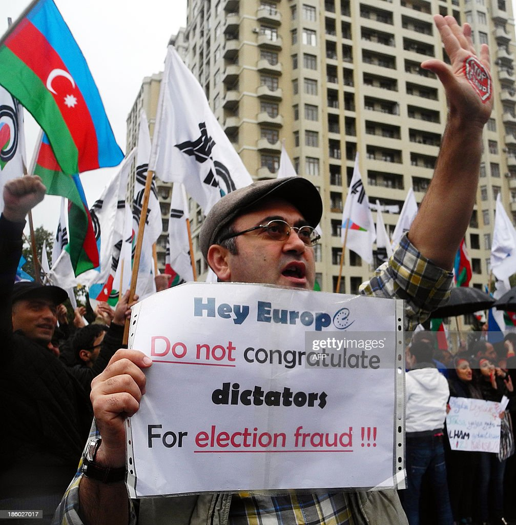 An Azerbaijani opposition supporter holds a placard reading 'Hey Europe, do not congratulate dictators for election fraud !!!' as he takes part in a demonstration in Baku, on October 27, 2013. Azerbaijani President Ilham Aliyev was sworn in for a third term on October 19, 2013 after romping to victory in a widely criticised election in the oil-rich ex-Soviet country. AFP PHOTO / TOFIK BABAYEV