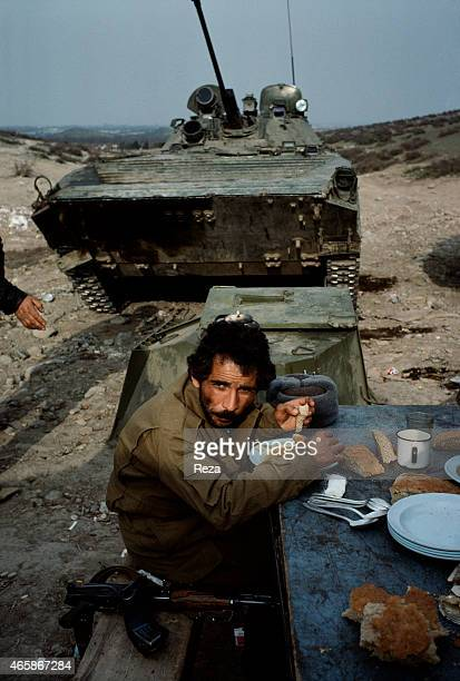 An Azerbaijani soldier eats a feeble lunch next to a tank at a makeshift Azerbaijani military base in the mountains of Karabakh Azerbaijan in March...