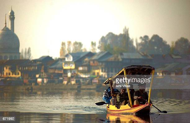 An canoe full of Indian army personnel makes its way across Srinagar's Dal Lake November 18 2001 in Kashmir India The war in Kashmir has been going...