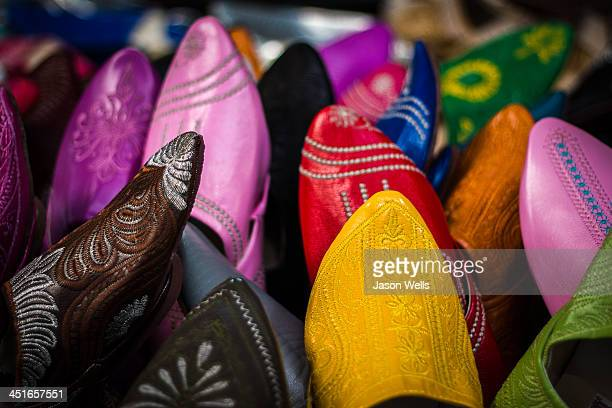 CONTENT] An closeup eyecatching image of soft leather slippers of all different colours being sold at the souk in Agadir Morocco