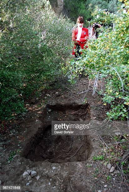 An LA Co Sheriff's department spokeswoman views the shallow grave dug by the parents and siblings of a five year old male in the Angeles National...