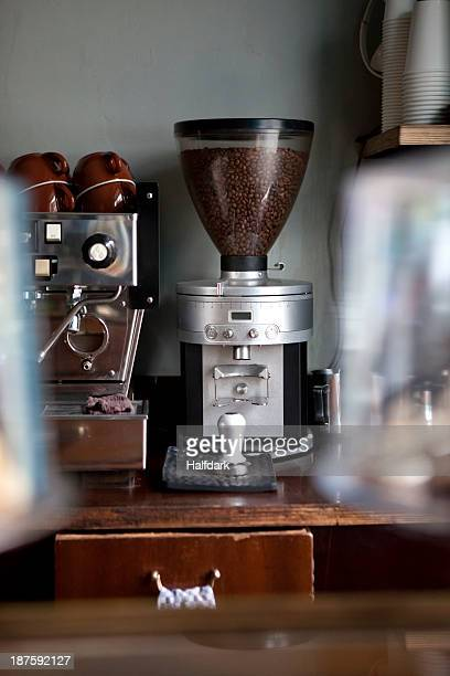 An coffee bean grinder next to an espresso maker in a coffee shop