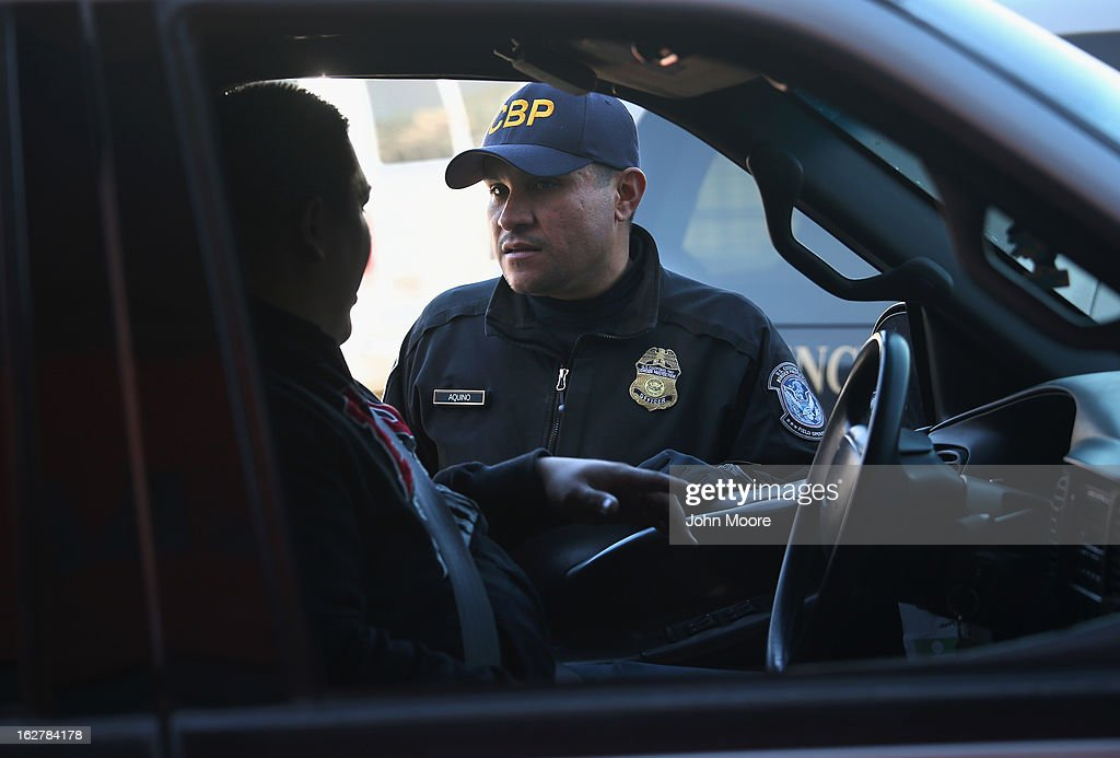 An Customs and Border Protection officer from the U.S. Office of Field Operations (OFO), speaks with a motorist crossing from Mexico into the United States on February 26, 2013 in Nogales, Arizona. Some 15,000 people cross between Mexico and the U.S. each day in Nogales, Arizona's busiest border crossing.