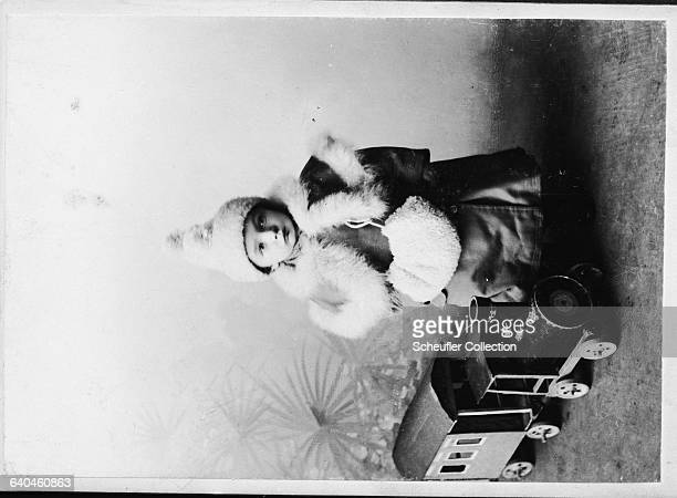 An Czech girl in winter clothes poses for a photograph in a studio with a toy train next to her