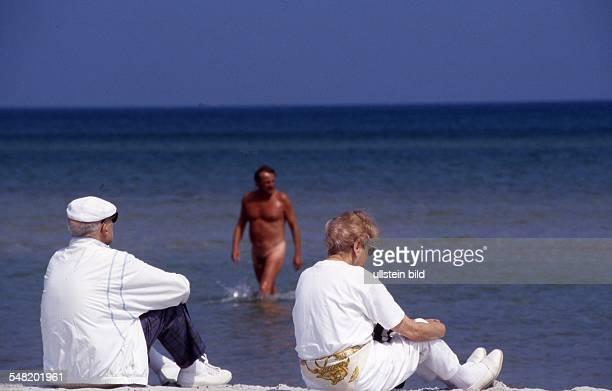 FKK an der Ostsee am Strand von Warnemünde bekleidete Urlauber sitzen am Strand 1999