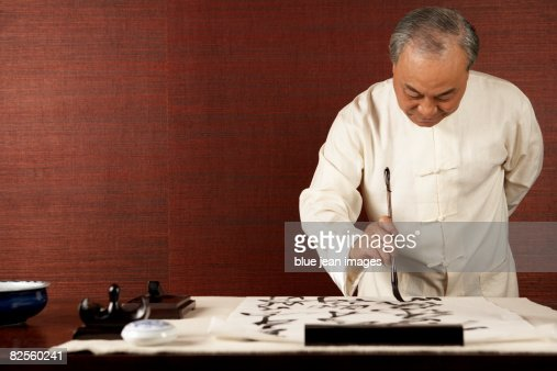 An distinguished gentleman practices the traditional art of Chinese calligraphy.