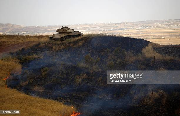 An disused Israeli tank is stationed on a burning mountain side in the ElRom settlement in the Israeliannexed Golan Heights on June 28 after it was...