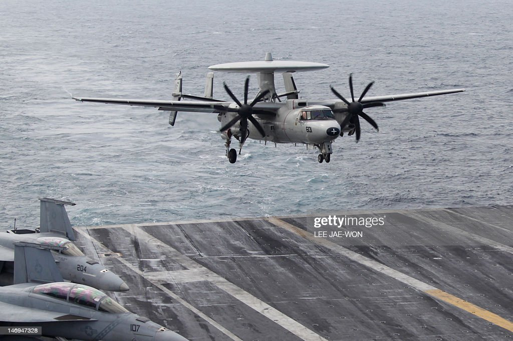 An E-2C Hawkeye lands onto the deck of the US aircraft carrier USS George Washington during joint military drills with South Korea in the Yellow Sea, southwest of Seoul on June 24, 2012. The three-day drill, which started on June 23, involves 10 South Korean warships plus the USS George Washington aircraft carrier, 8,000 personnel and hundreds of combat aircraft, South Korea's defence ministry said. AFP PHOTO / POOL / Lee Jae-Won
